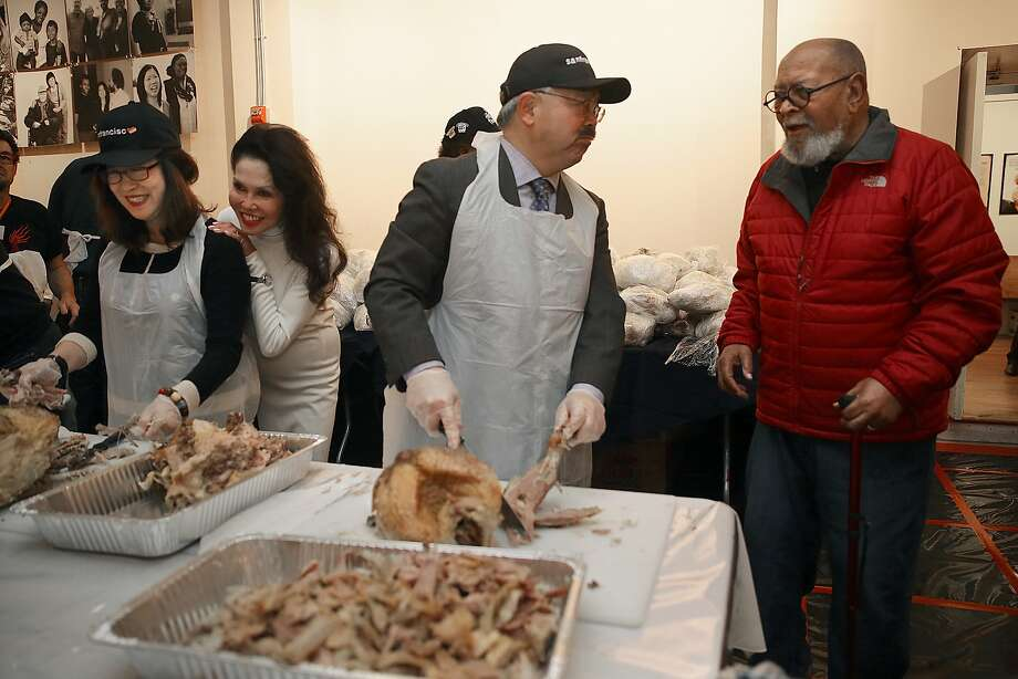 Anita Lee (left) with Janice Mirikitani and mayor Ed Lee (middle) talks with Cecil Williams (right) while carving turkey in Freedom Hall at Glide Memorial in San Francisco, California, on Thursday, November 26, 2015. Photo: Liz Hafalia, The Chronicle