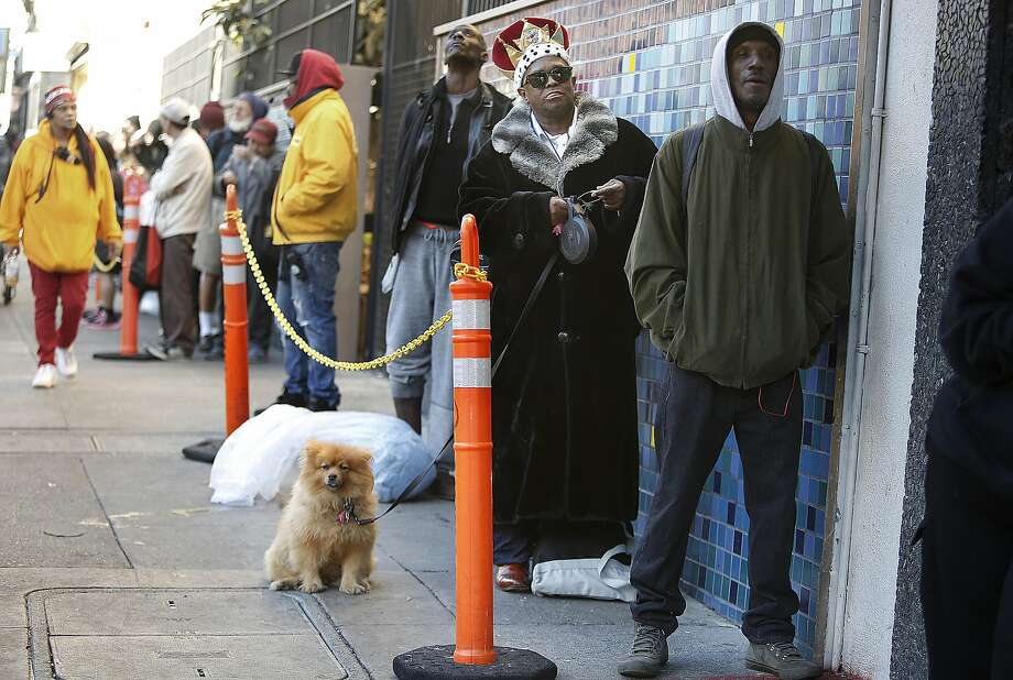 Steven Royson (middle) with his dog Oscar and Deshawn Bunton (right) wait in line for a thanksgiving meal at Glide Memorial in San Francisco, California, on Thursday, November 26, 2015. Photo: Liz Hafalia, The Chronicle