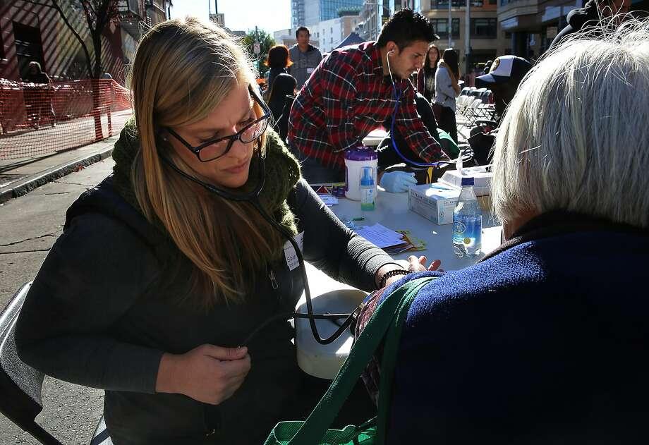 San Francisco City Impact volunteer  Patricia Baierlang (middle left), nurse practitioner, takes the pulse of an elderly woman on Jones St. in San Francisco, California, on Thursday, November 26, 2015. Photo: Liz Hafalia, The Chronicle