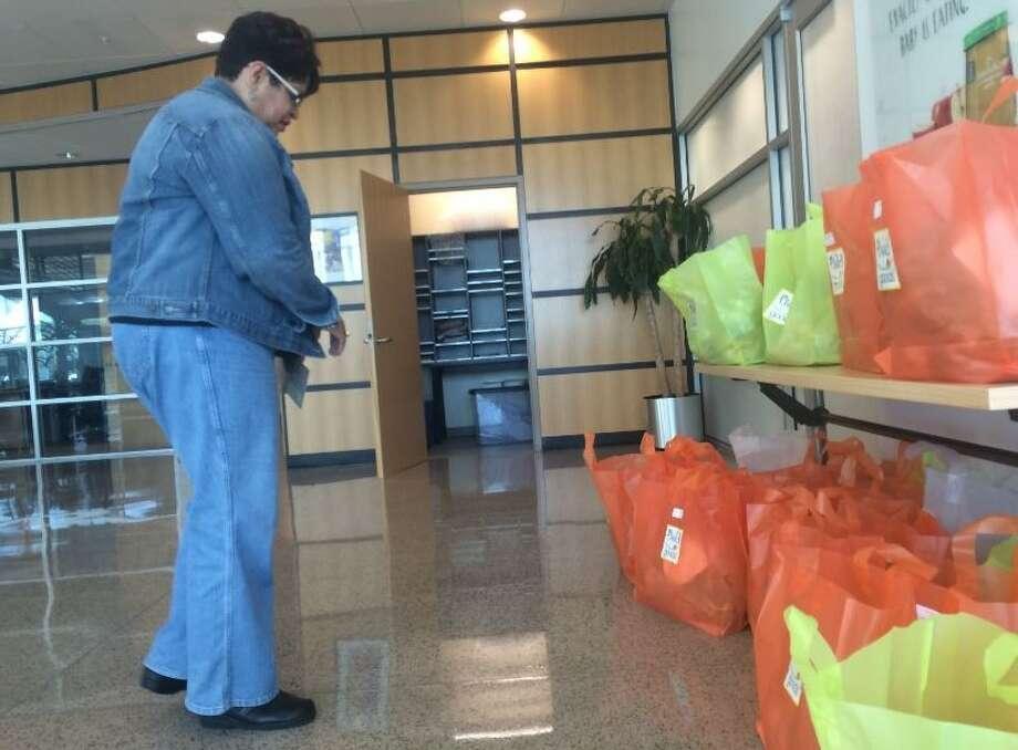 Elaine Santiago, a Beech-Nut consumer services representative, picks up her weekly Field Goods bag of produce on Friday, Nov. 20. (Lindsay Ellis/Times Union) Photo: Ellis, Lindsay