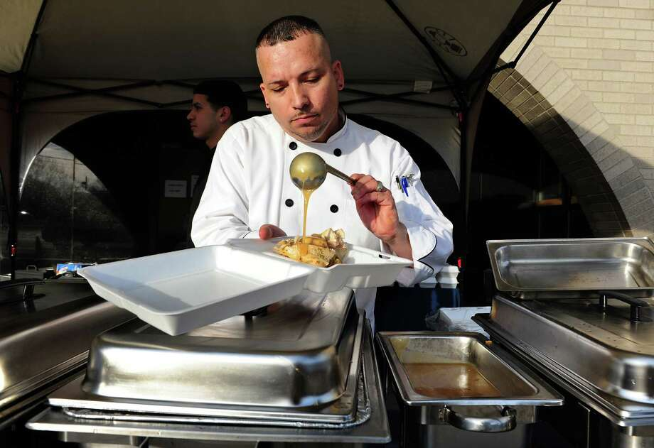 Chef Michel Martinez loads up a container with Thanksgiving Day food for Bridgeport Police Department officers and anyone else who happen to walk past in front of police headquarters on Congress Street in Bridgeport, Conn. on Thursday Nov. 26, 2015. Martinez, who owns Festive Food Caterers, and his worker Jorge Sepulveda, came out to serve the holiday dinners to all police department personel. Photo: Christian Abraham / Hearst Connecticut Media / Connecticut Post