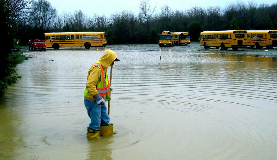 SPECTRUM/As school buses make their exits Tuesday for their afternoon runs, Public Works employee Dylan Tuz hunts for a blocked drain in the flooded parking lot of All Star Transportation along Dodd Road in New Milford. Flooding occurred when a retention pond on the Litchfield Crossings shopping center construction site just west of the bus lot breached due to heavy rains. March 30, 2010 Photo: Norm Cummings / The News-Times