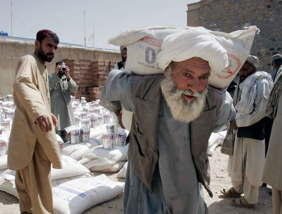 "FILE - In this May 10, 2009, file photo, an Afghan man carries a sack of wheat distributed to poor displaced families of Helmand province in the city of Kandahar province south of Kabul, Afghanistan. With Washington set to send billions of dollars in fresh aid to Afghanistan despite the military drawdown, the U.S. official in charge of auditing assistance programs says ""it's not too late"" to address the fraud and mismanagement that has bedeviled the 14-year effort to rebuild the country. (AP Photo/Allauddin Khan, File) ORG XMIT: CAIMA501 Photo: Allauddin Khan / AP"