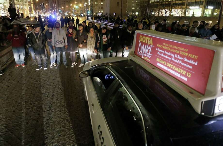 Protesters block rush hour traffic along the Michigan Ave. bridge over the Chicago River Wednesday, Nov. 25, 2015, in Chicago, the day after murder charges were brought against police officer Jason Van Dyke in the killing of 17-year-old Laquan McDonald. (AP Photo/Charles Rex Arbogast) ORG XMIT: ILCA112 Photo: Charles Rex Arbogast / AP