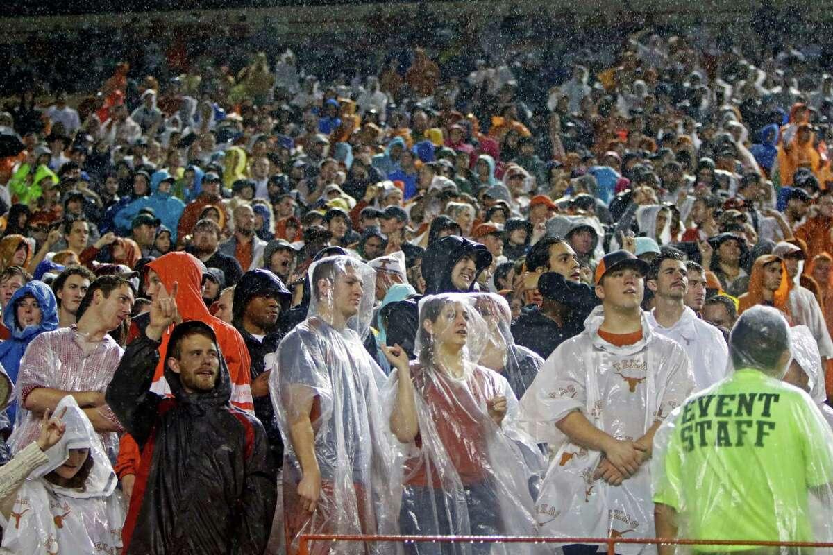 Texas fans stand in the rain during the first half of an NCAA college football game against Texas Tech, Thursday, Nov. 26, 2015, in Austin, Texas. (AP Photo/Michael Thomas)