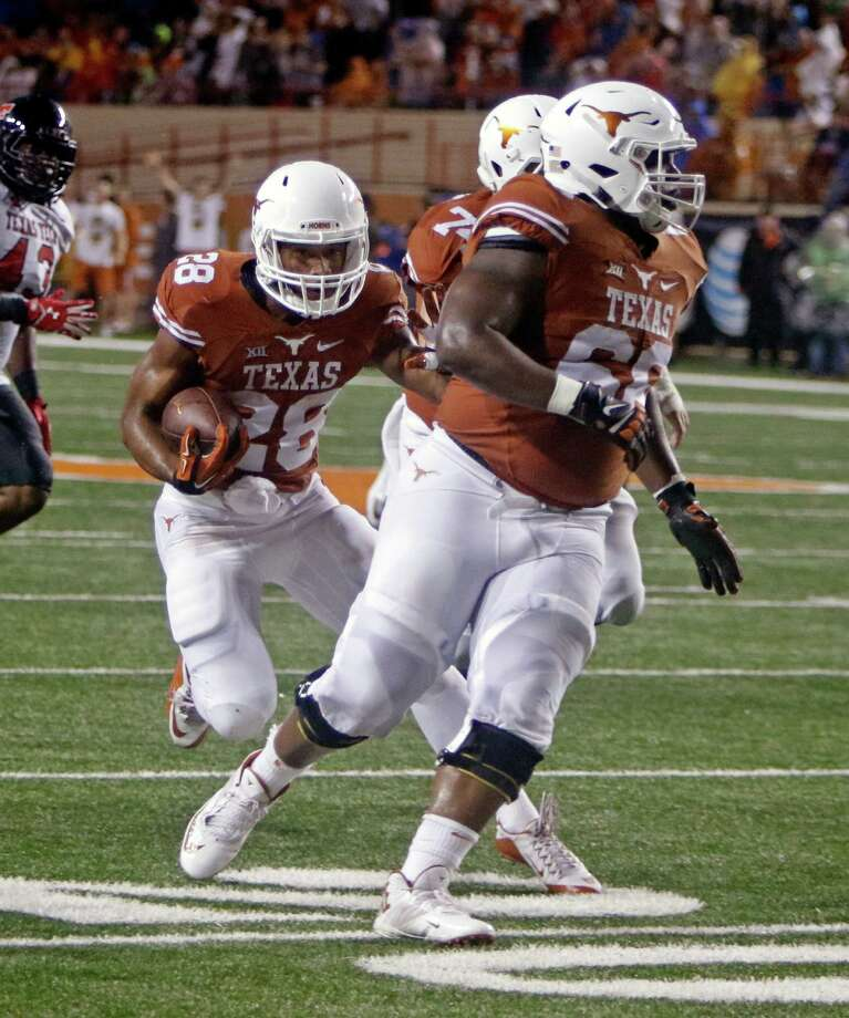 Texas running back Kirk Johnson (28) runs behind blockers Sedrick Flowers (66) and Taylor Doyle during the first half of an NCAA college football game against Texas Tech, Thursday, Nov. 26, 2015, in Austin, Texas. (AP Photo/Michael Thomas) Photo: Michael Thomas, FRE / Associated Press / FR65778 AP