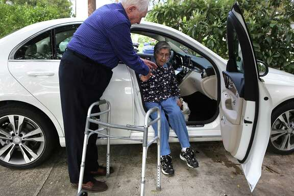 "Dick Busacker, a driver with ""Call A Ride for Seniors,"" helps Ana Jeffery, 87, get in his car on the way to a doctor's appointment on Nov. 11."