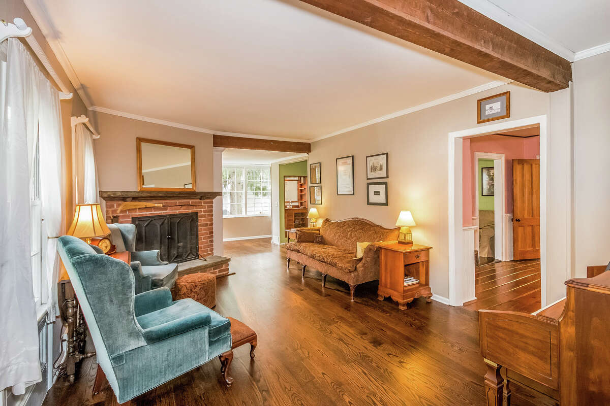The living room features a fireplace and ceiling beams.