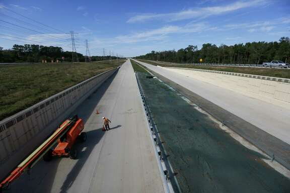 A construction worker moves cones for a lift on the Grand Parkway Thursday, Nov. 12, 2015, in Houston. The section of the Grand Parkway from from U.S. 290 to U.S. 59 is nearing completion and expected to open soon.