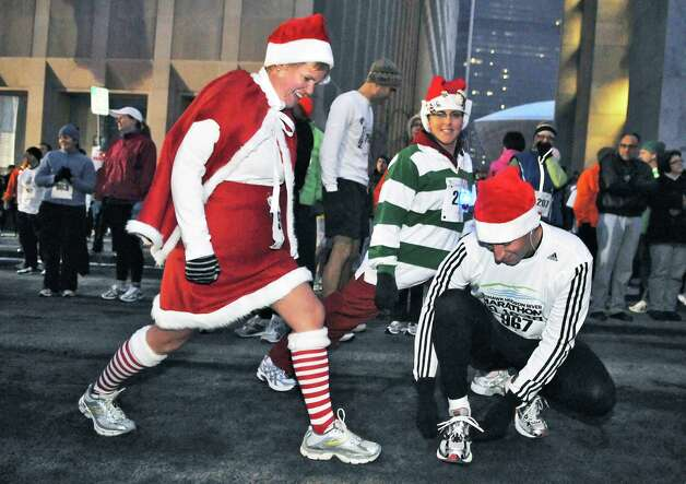 Stacey Whiteley, left, Paula Dibiase and Mike Whiteley, at right, all of Delmar, ready for the 14th annual Last Run 5K through the city of Albany Saturday evening December 18, 2010.  (John Carl D'Annibale / Times Union) Photo: John Carl D'Annibale / 00011216A