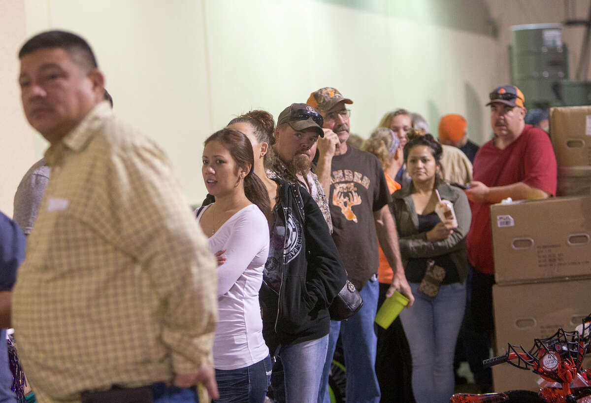Customers line up outside Academy Sports + Outdoors before they open, Friday, Nov. 27, 2015, in Pearland.