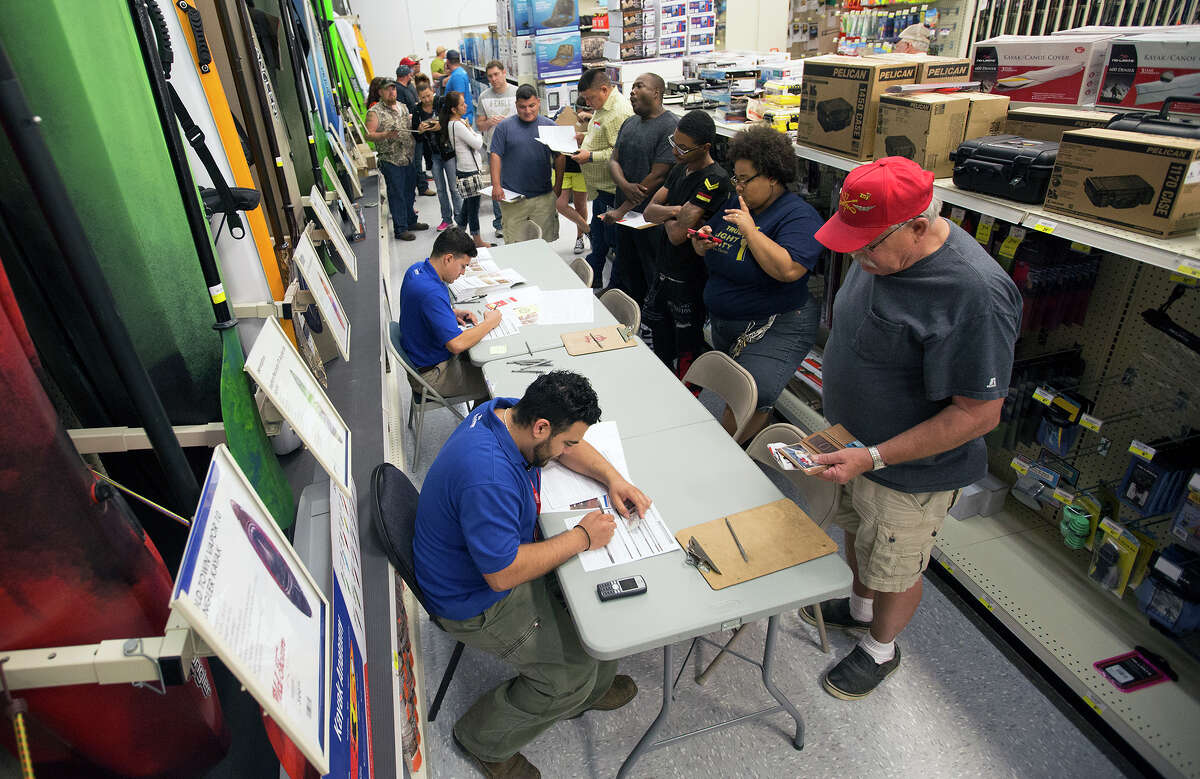 Jerry Trembath, right, waits to purchase a firearm Academy Sports + Outdoors during Black Friday, Nov. 27, 2015, in Pearland.