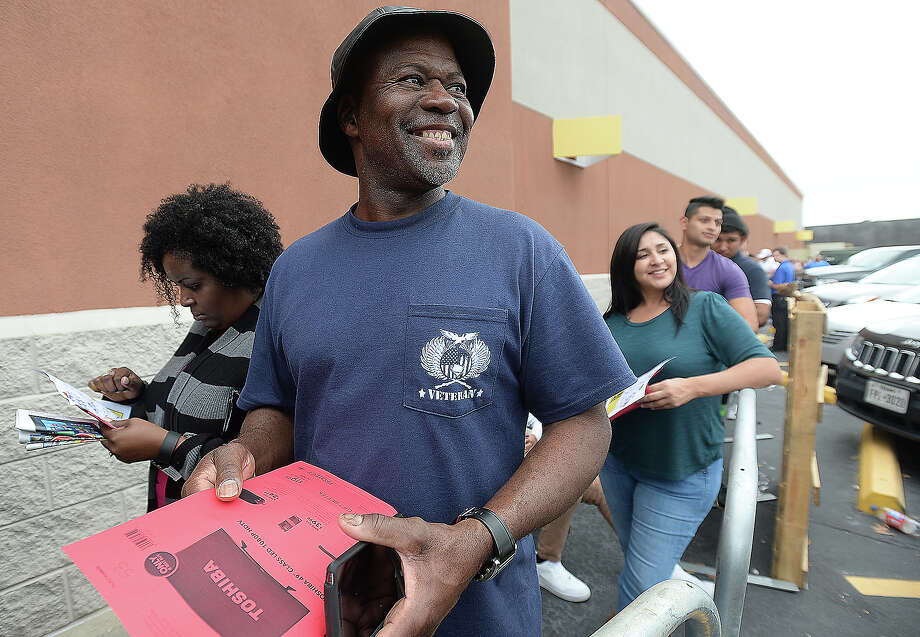 """Jessie Hawkins jokes with Best Buy employees as they work the line before doors open as early shopping gets underway on Thanksgiving. Hawkins waited with his niece Aquana Baines (left) and were among the last of the shoppers, including Estella Lopez (right) to make the cut for the 49"""" television special sale.  Photo taken Thursday, November 26, 2015  Kim Brent/The Enterprise Photo: Kim Brent / Beaumont Enterprise"""