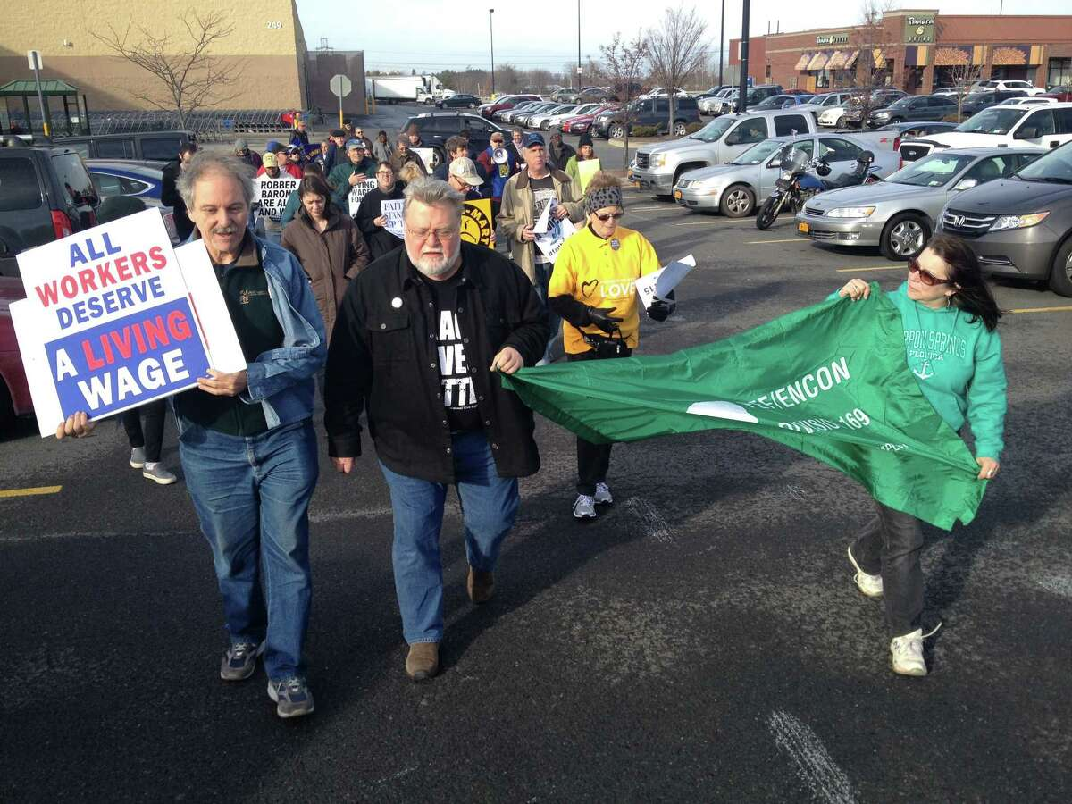 About 50 demonstrators protested Friday morning in front of the East Greenbush Walmart store over the firing of Thomas Smith, 52, of Albany, on Nov. 6 for redeeming $2 worth of empty cans and bottles left behind in a shopping cart in a breezeway near the redemption machines. They also delivered a petition with 2,045 signatures demanding that Smith is rehired, paid back wages and issued an apology. (Photo courtesy of Emily McNeill)