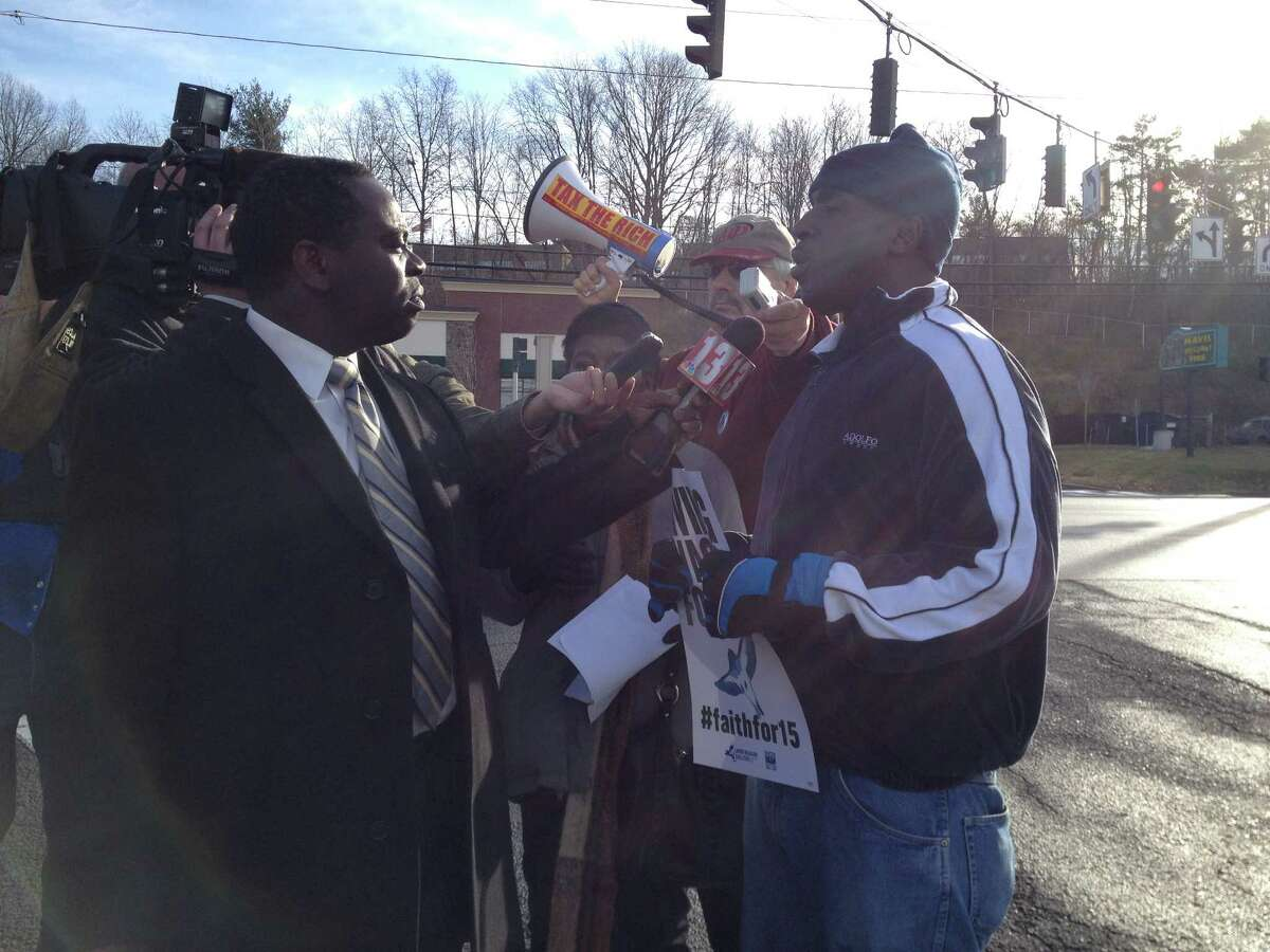 Thomas Smith speaks to the media Friday morning in front of the East Greenbush Walmart store. About 50 people demonstrated against the firing of Smith, 52, of Albany, on Nov. 6 for redeeming $2 worth of empty cans and bottles left behind in a shopping cart in a breezeway near the redemption machines. They also delivered a petition with 2,045 signatures demanding that Smith is rehired, paid back wages and issued an apology. (Photo courtesy of Emily McNeill)