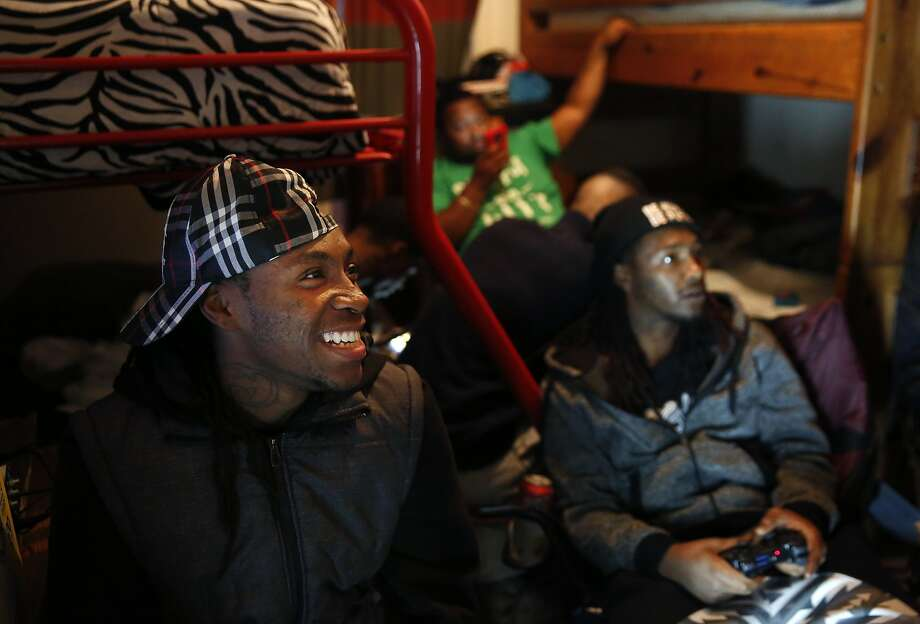 Treyvon Coulter (left), who says he's been stopped frequently by police, plays Grand Theft Auto with his brothers and cousins. Photo: Leah Millis, The Chronicle
