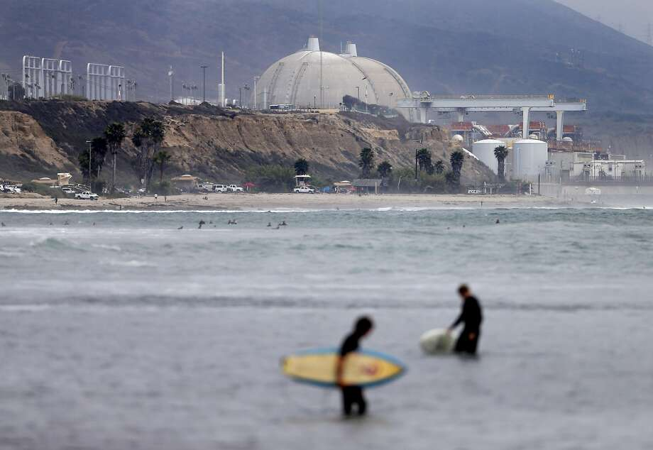 FILE - In this June 7, 2013 file photo, surfers pass in front of the San Onofre nuclear power plant in San Onofre, Calif.  Federal regulators have closed a case that questioned whether Southern California Edison violated government rules when it installed faulty equipment at the now-closed San Onofre nuclear power plant. (AP Photo/Gregory Bull, File) Photo: Gregory Bull, AP