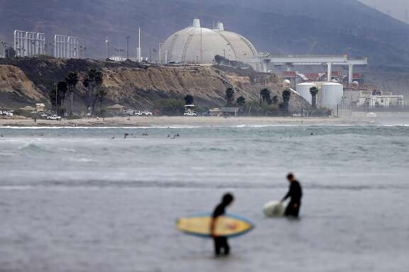 FILE - In this June 7, 2013 file photo, surfers pass in front of the San Onofre nuclear power plant in San Onofre, Calif.  Federal regulators have closed a case that questioned whether Southern California Edison violated government rules when it installed faulty equipment at the now-closed San Onofre nuclear power plant. (AP Photo/Gregory Bull, File)