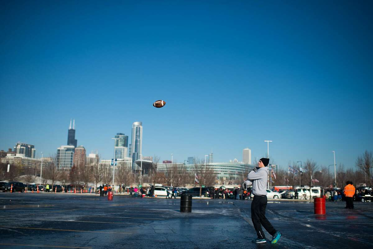 Michael Varzino throws a pass to a friend in the parking lot south of Soldier Field before a Chicago Bears game Sunday, Nov. 22, 2015 in Chicago, IL. The south parking lot is where the Lucas Museum of Narrative Art is proposed to be built. (Rob Hart/For the San Francisco Chronicle)