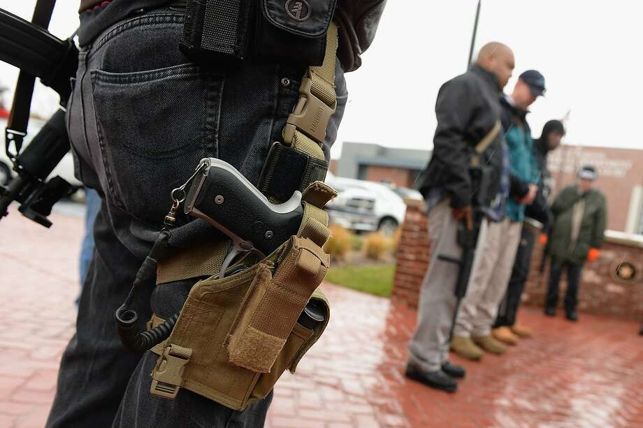 Open carry gun activists participate in a march in front of the city police department and minicipal court on November 16, 2015 in Ferguson, Missouri.  About a dozen supporters of gun rights gathered in Ferguson November 16 for what organizers hoped would be a racially integrated open-carry march to demonstrate that Second Amendment rights are for everybody.  AFP PHOTO / MICHAEL B. THOMASMichael B. Thomas/AFP/Getty Images Photo: Michael B. Thomas, AFP / Getty Images