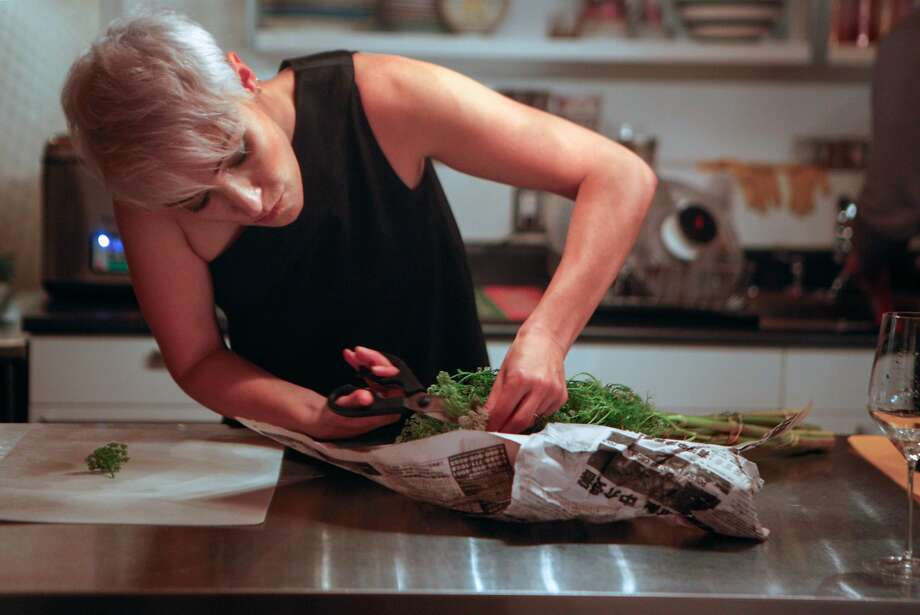Jeanne Feldkamp preparing flowers for the Hearsay Supper Club 6-course dinner they will host for the evening on November 21, 2015.  A 12-person, usually themed, dinner for strangers in their home for around $120 with a constantly changing menu. Photo: Franchon Smith, The Chronicle