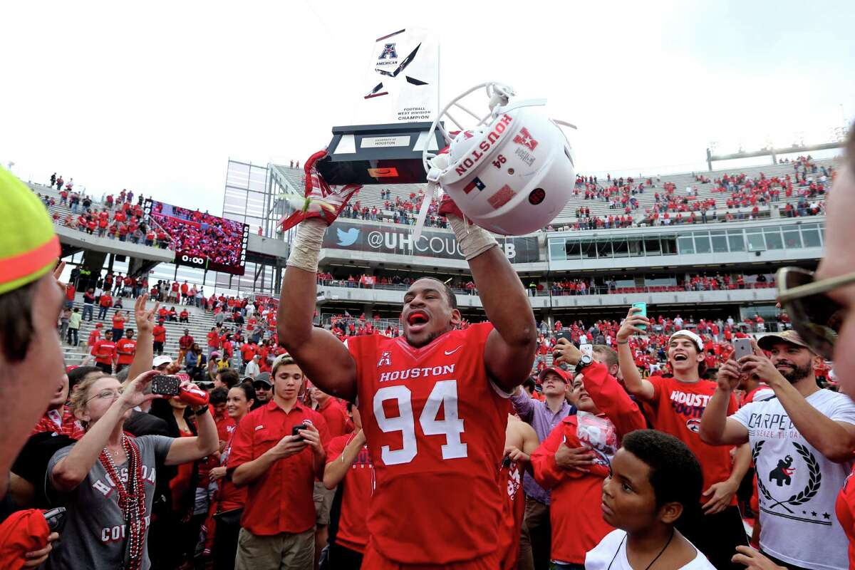 Houston Cougars defensive end Cameron Malveaux (94) hoists the AAC West Division Title trophy at the conclusion of their 52-31 win over the Navy Midshipmen in a NCAA college football game at TDECU Stadium Friday, Nov. 27, 2015, in Houston, Texas. Houston clinched the AAC West Division Title.