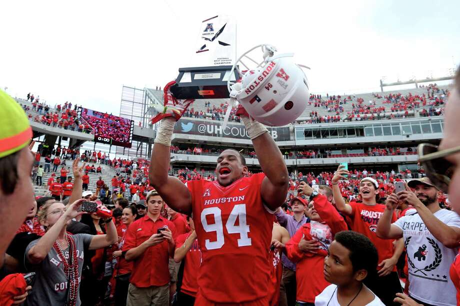 Houston Cougars defensive end Cameron Malveaux (94) hoists the AAC West Division Title trophy at the conclusion of their 52-31 win over the Navy Midshipmen in a NCAA college football game at TDECU Stadium Friday, Nov. 27, 2015, in Houston, Texas. Houston clinched the AAC West Division Title. Photo: Gary Coronado, Houston Chronicle / © 2015 Houston Chronicle