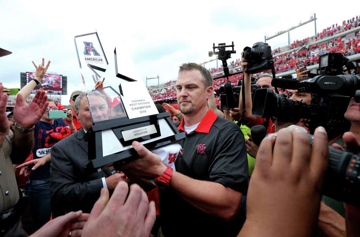 Houston Cougars head coach Tom Herman shown with the AAC West Division Title trophy at the conclusion of their 52-31 win over the Navy Midshipmen in a NCAA college football game at TDECU Stadium Friday, Nov. 27, 2015, in Houston, Texas. Houston clinched the AAC West Division Title.