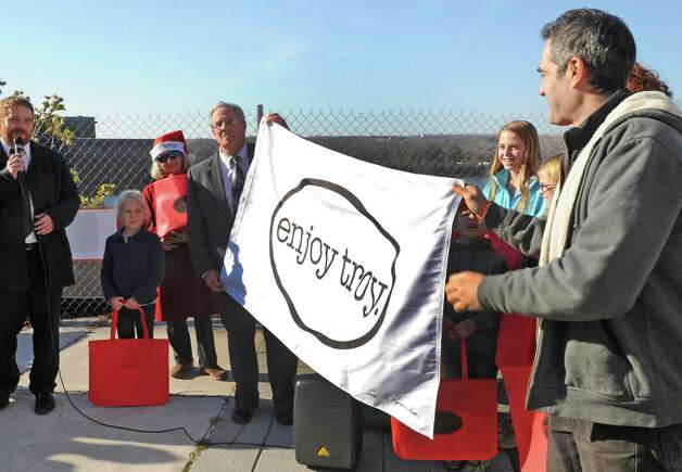 Mayor Lou Rosamilia, left, and Vic Christopher unveil an Enjoy Troy flag during a Troy is open for business holiday ceremony on Wednesday Nov. 25, 2015 in Troy, N.Y. (Michael P. Farrell/Times Union) Photo: Michael P. Farrell / 10034429A