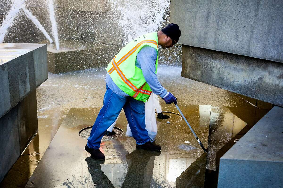 Department of Public Works labor worker, Tai Auimatagi, collects a dirty needle from a fountain, at UN Plaza, in San Francisco, California on Friday, November 20, 2015. He says when he arrives at work, the first thing he does is get rid of the used needles.
