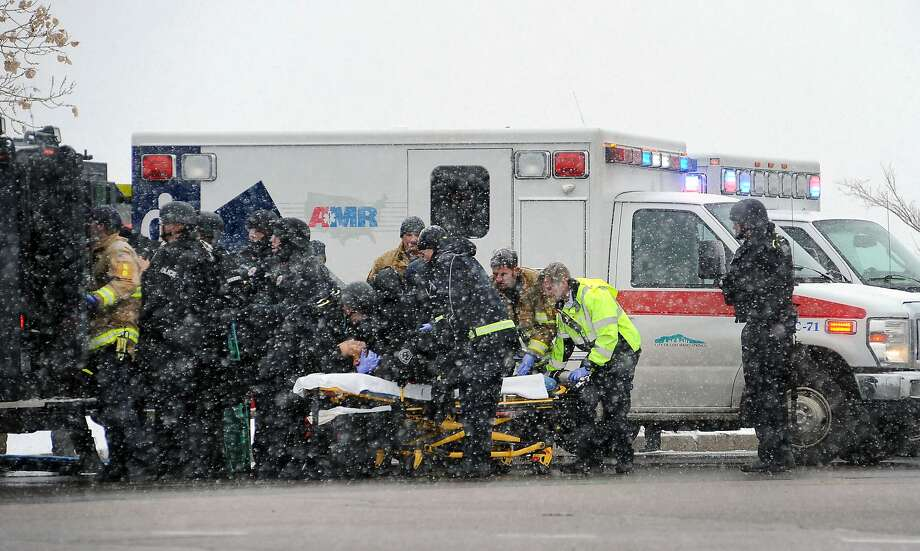 Emergency personnel transport an officer to an ambulance after reports of a shooting near the Planned Parenthood clinic Friday, Nov, 27, 2015, in Colorado Springs, Colo. According to authorities multiple injuries have been reported. (Daniel Owen/The Gazette via AP) MAGS OUT; MANDATORY CREDIT Photo: Daniel Owen, Associated Press