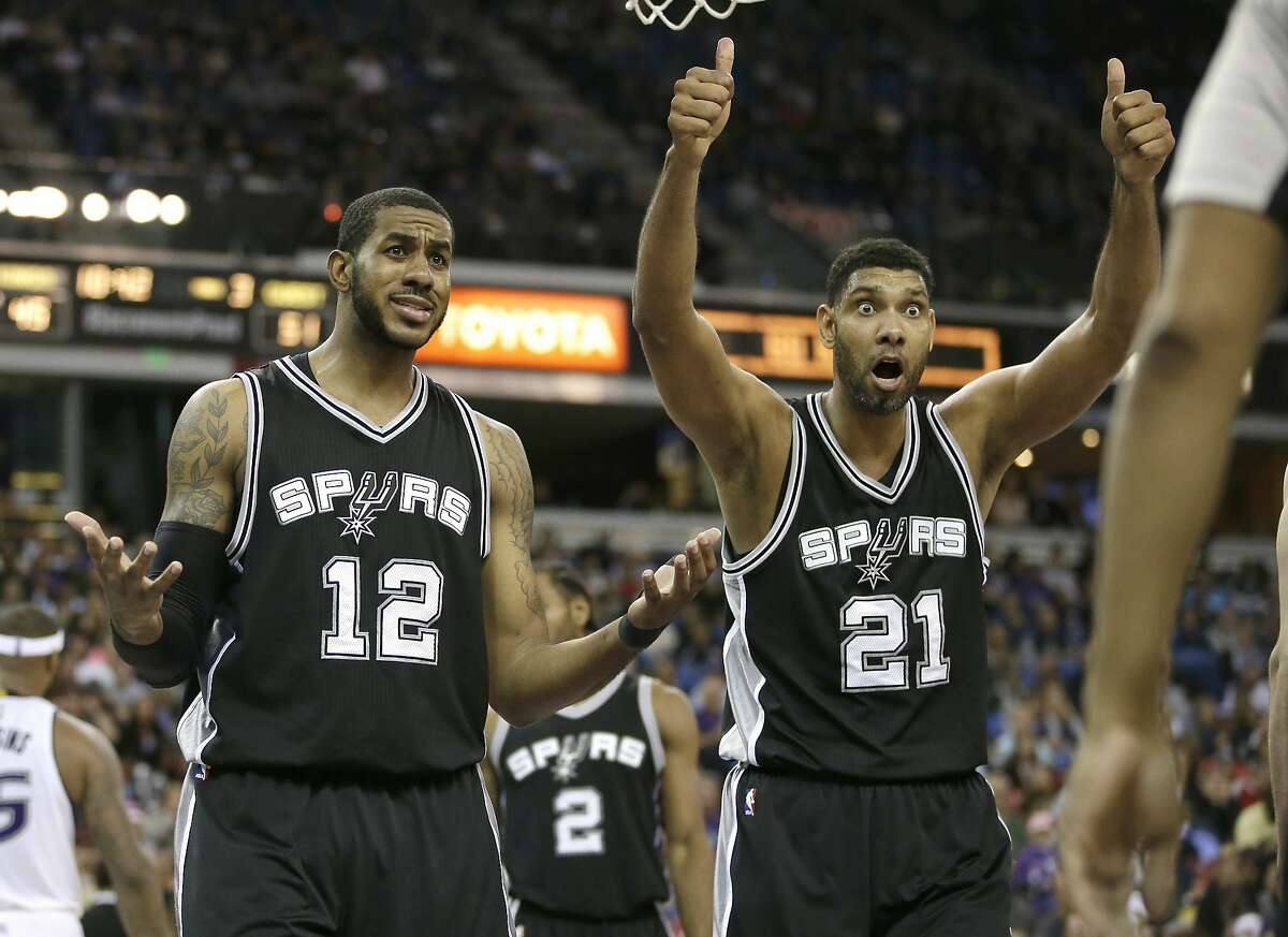 San Antonio Spurs' LaMarcus Aldridge, left, and Tim Duncan, question official Bennie Adams after he called Aldridge for a foul during the second half of an NBA basketball game against the Sacramento Kings in Sacramento, Calif., Monday, Nov. 9, 2015. (AP Photo/Rich Pedroncelli)