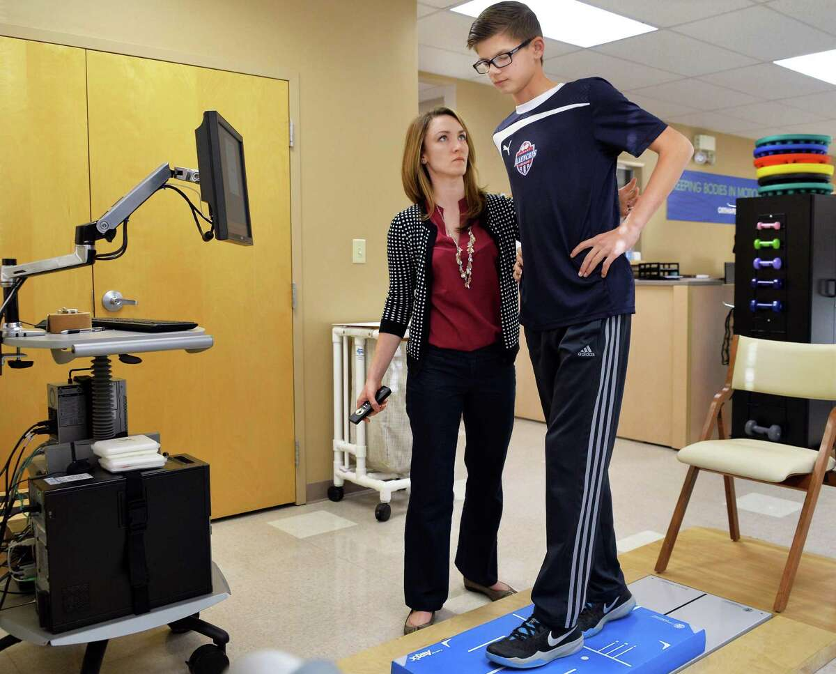 Physical therapist Audrey Paslow, left, repeats a baseline stability evaluation test for Conor Van Sise, 14, of the Albany Alleycats soccer club, at Ellis Medicine Friday Nov.20, 2015 in Clifton Park, NY. (John Carl D'Annibale / Times Union)
