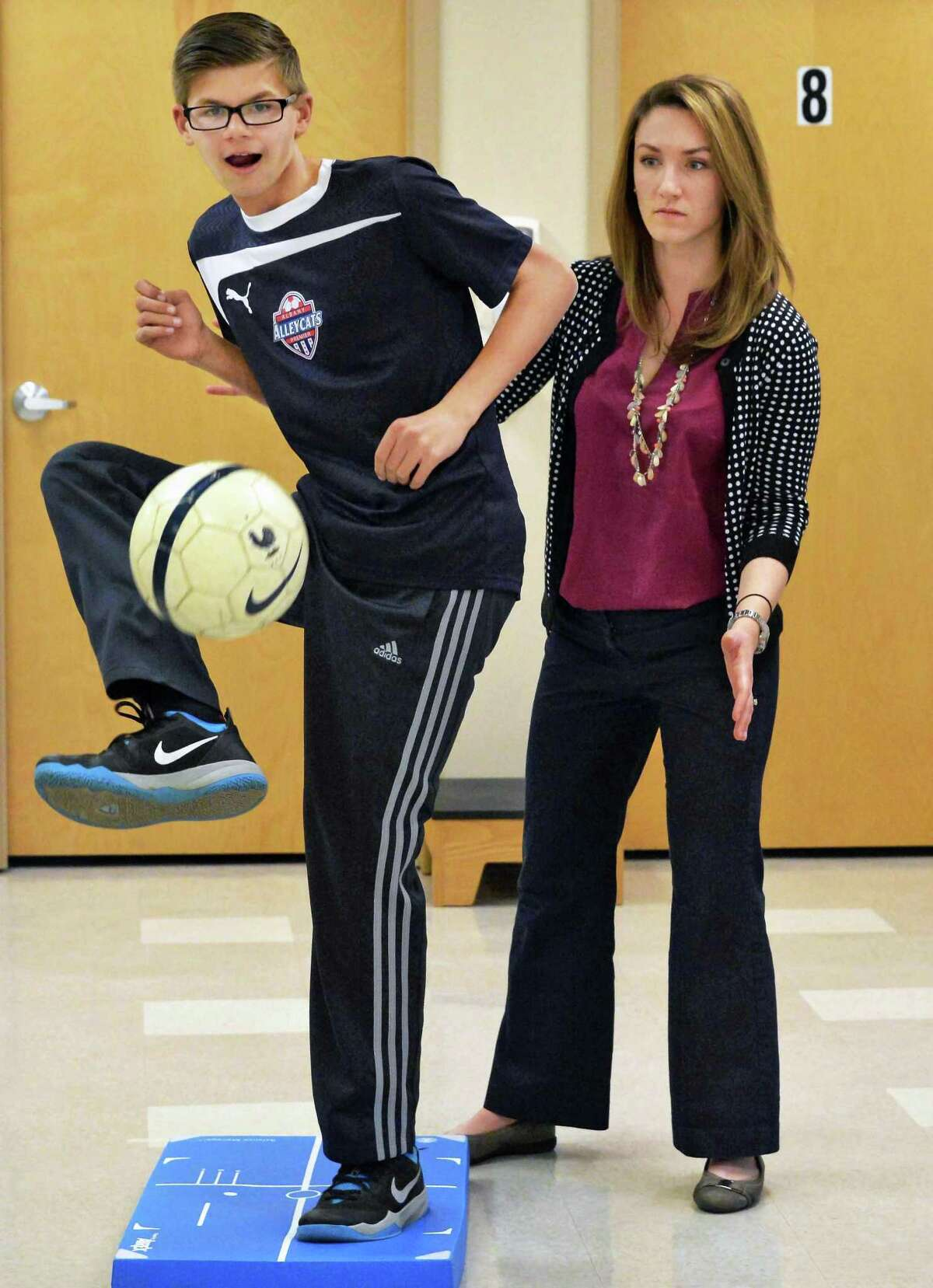 Physical therapist Audrey Paslow, right, conducts a sports readiness exercise with Conor Van Sise, 14, of the Albany Alleycats soccer club, at Ellis Medicine Friday Nov.20, 2015 in Clifton Park, NY. (John Carl D'Annibale / Times Union)