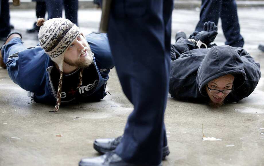 "Two men are detained near Pioneer Court on Friday, Nov. 27, 2015, in Chicago. Community activists and labor leaders held a demonstration billed as a ""march for justice"" in the wake of the release of video showing an officer fatally shooting Laquan McDonald. Photo: Nam Y. Huh, Associated Press"