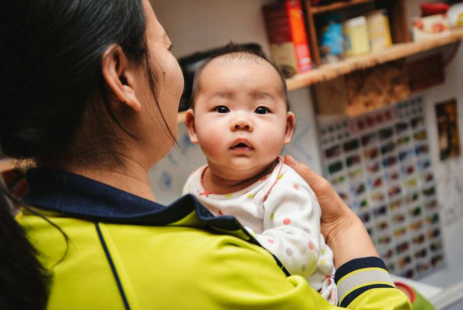 Ivy Gao with her daughter Sophia, 4 months, in their unit  in a Chinatown single-room occupancy hotel. Photo: Tudor Stanley
