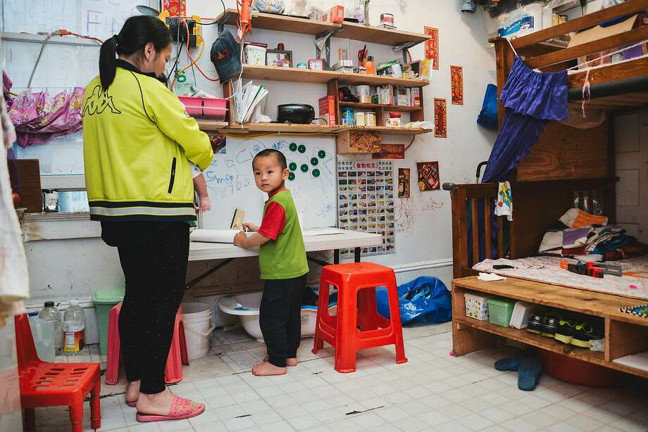 Ivy Gao with her daughter Sophia, 4 months, and her son Sampson, 3, in their unit  in a Chinatown single-room occupancy hotel. Photo: Tudor Stanley