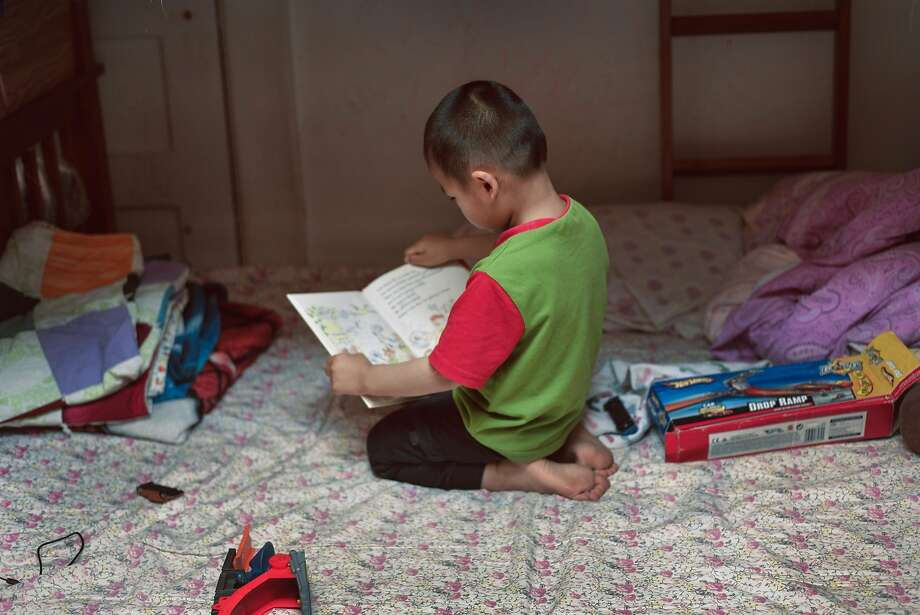 Ivy Gao's son Sampson, 3, reads in their unit  in a Chinatown single-room occupancy hotel. Photo: Tudor Stanley