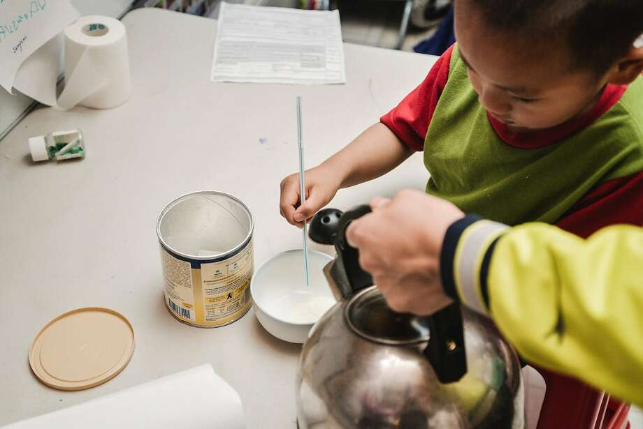 Ivy Gao makes a meal for son Sampson, 3, in their unit  in a Chinatown single-room occupancy hotel. Photo: Tudor Stanley
