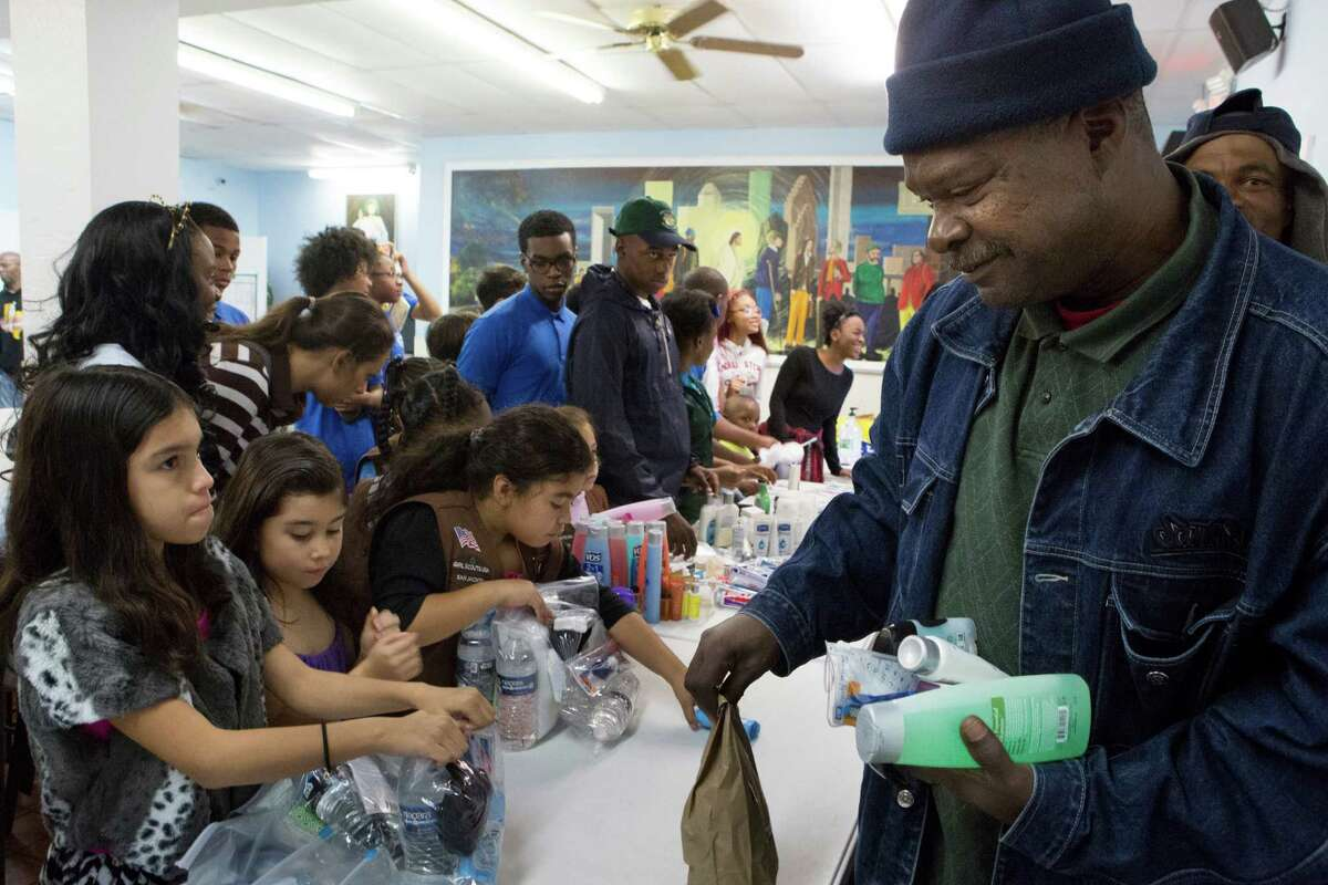 Al Sagers, 58, right, receives personal hygiene products from Girl Scout Brownies during an event organized by Theragood Deeds to help individuals struggling with poverty with a warm meal, warm clothing and hygiene products.