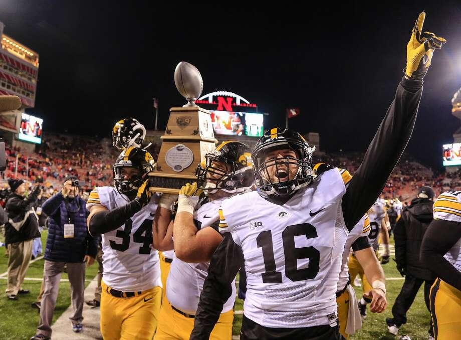 Iowa's Nate Meier (34) and Dillon Kidd (16) show off the Heroes Trophy. Photo: Nati Harnik, Associated Press