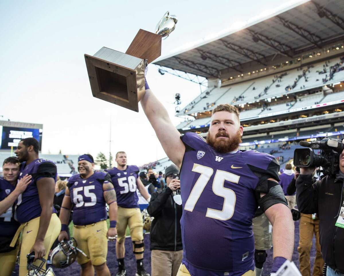 Offensive lineman Jesse Sosebee #75 of the Washington Huskies walks off the field with the Apple Cup after the Huskies defeated the Washington State Cougars in a football game at Husky Stadium on November 27, 2015 in Seattle, Washington. The Huskies won the game 45-10.
