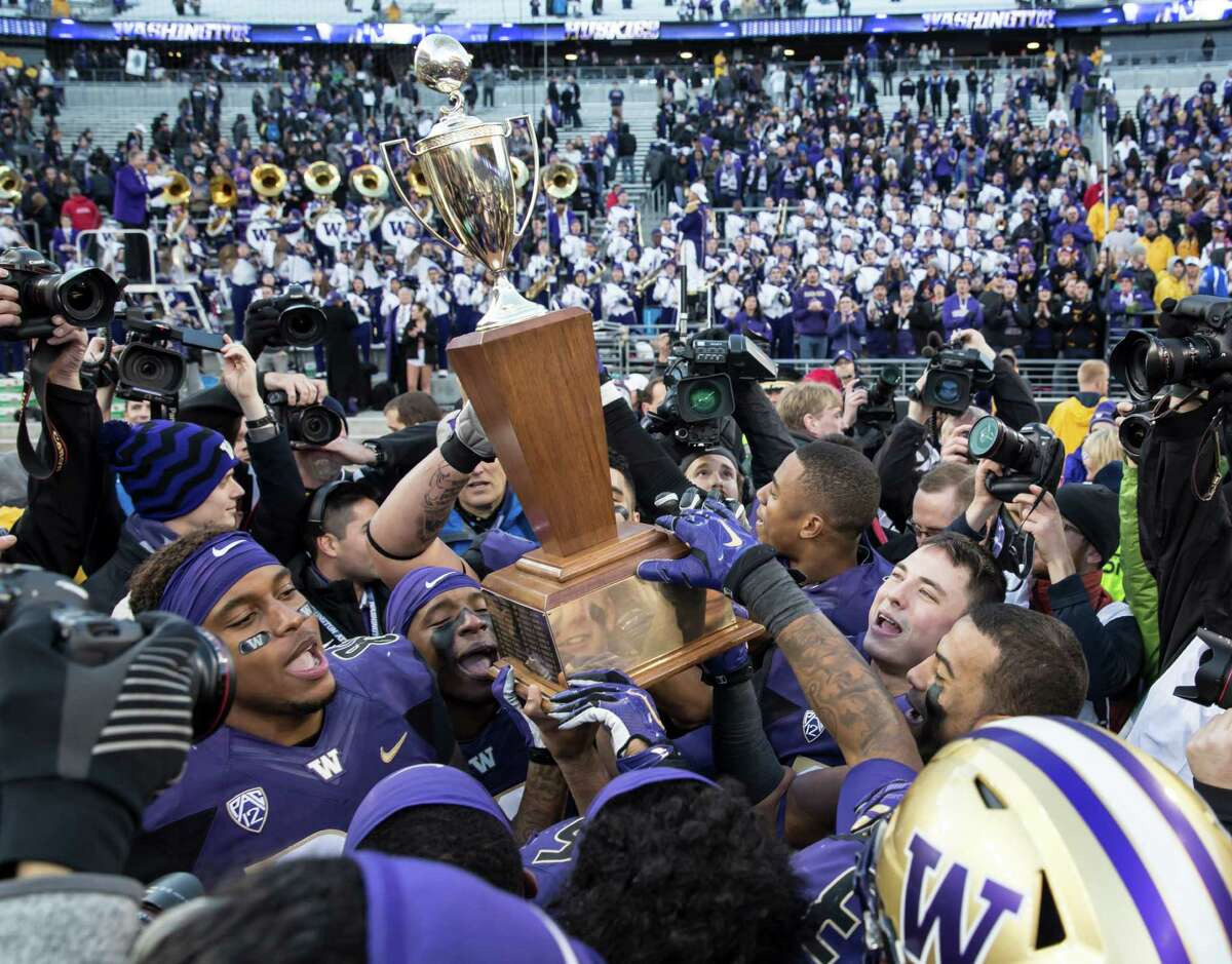 Members of the Washington Huskies celebrate defeating the Washington State Cougars during a football game to win the Apple Cup at Husky Stadium on November 27, 2015 in Seattle, Washington. The Huskies won the game 45-10.