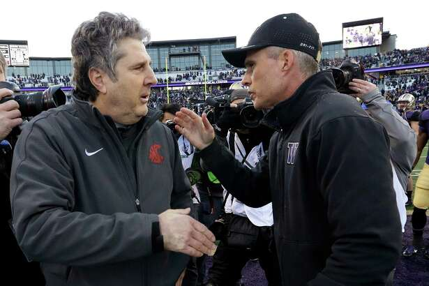 Washington State coach Mike Leach, left, is greeted by Washington coach Chris Petersen after an NCAA college football game Friday, Nov. 27, 2015, in Seattle. Washington won the annual Apple Cup, 45-10. (AP Photo/Elaine Thompson)