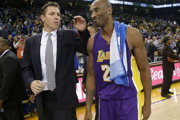 Golden State Warriors interim coach Luke Walton, left, walks off the court with Los Angeles Lakers guard Kobe Bryant after an NBA basketball game in Oakland, Calif., Tuesday, Nov. 24, 2015. The Warriors won 111-77. (AP Photo/Jeff Chiu)