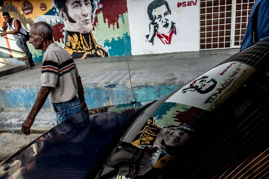 A man walks next to propaganda graffiti showing South American independence hero Simon Bolivar (left) and former Venezuelan President Hugo Chavez in a Caracas shantytown. Photo: Federico Parra, AFP / Getty Images
