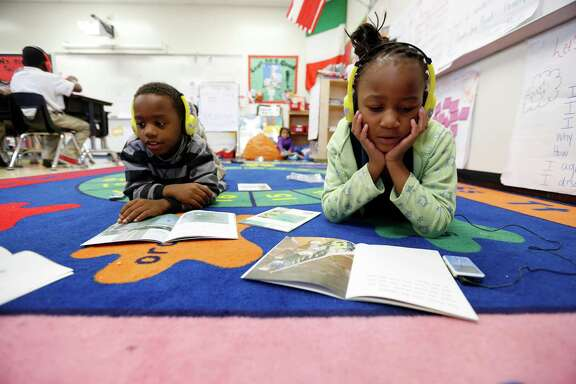 First-graders Da-Quarius King (right-left) and Davida Sweat use radio books as part of HISD's reading initiative, Literacy by 3.