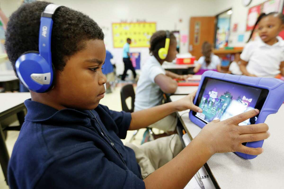 Mading Elementary first-grader Christian Simmons works on a reading activity on an iPad during a November class. The program allows his teacher, Zakiya Martin, to log on and check his progress later.