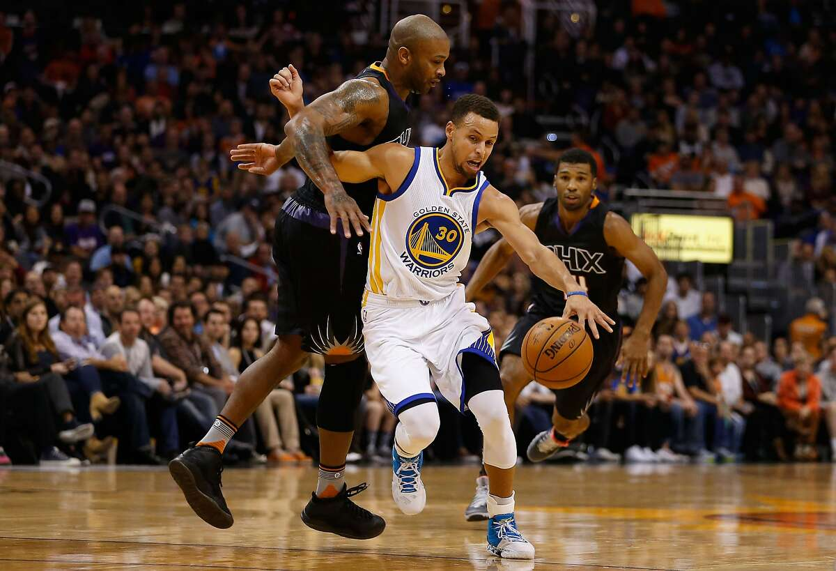 Stephen Curry #30 of the Golden State Warriors is fouled as he drives past P.J. Tucker #17 of the Phoenix Suns during the first half of the NBA game at Talking Stick Resort Arena on November 27, 2015 in Phoenix, Arizona.