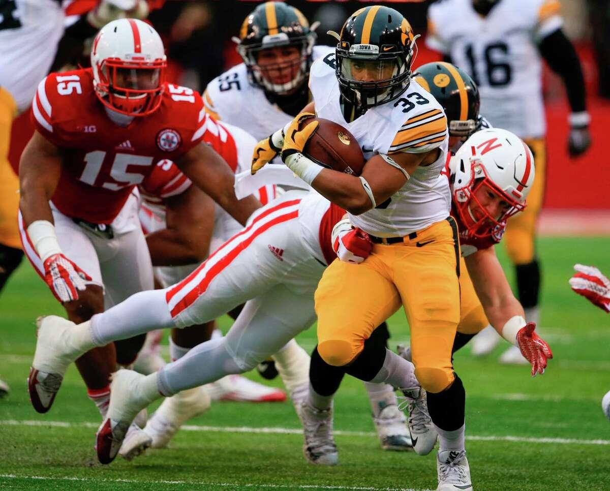 Iowa running back Jordan Canzeri (33) breaks a tackle by Nebraska linebacker Chris Weber (49) during the first half of an NCAA college football game in Lincoln, Neb., Friday, Nov. 27, 2015. (AP Photo/Nati Harnik) ORG XMIT: NENH116